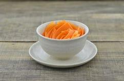 Adorne la taza con las zanahorias de las rebanadas en la tabla de madera Foto de archivo libre de regalías