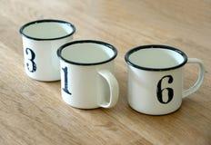 Adorne la taza del cinc en la tabla de madera Foto de archivo