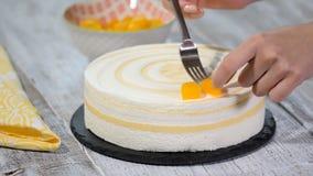 Adorne la torta de la crema batida con los melocotones de los pedazos metrajes