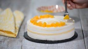 Adorne la torta de la crema batida con los melocotones de los pedazos almacen de metraje de vídeo