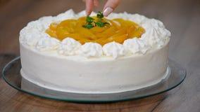 Adorne la torta del melocotón con las hojas de menta metrajes