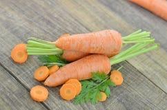 Adorne la zanahoria y las rebanadas frescas en la tabla de madera Foto de archivo libre de regalías