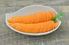 Adorne la zanahoria y las rebanadas frescas en la tabla de madera Fotos de archivo libres de regalías