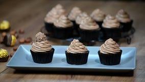 Adorne las magdalenas del chocolate con el caramelo almacen de metraje de vídeo