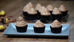 Adorne las magdalenas del chocolate con el caramelo almacen de video
