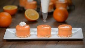 Adorne las mini tortas anaranjadas con crema azotada almacen de metraje de vídeo