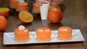 Adorne las mini tortas con crema azotada anaranjada almacen de video