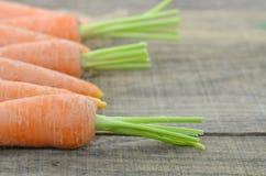 Adorne las zanahorias de la frescura en la tabla de madera rústica Fotografía de archivo