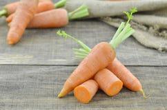 Adorne las zanahorias y los cortes frescos en la tabla de madera Imágenes de archivo libres de regalías
