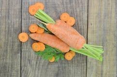 Adorne las zanahorias y las rebanadas frescas en la tabla de madera Fotografía de archivo libre de regalías