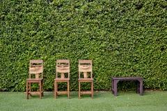 Adorne tres sillas y mesas de centro de madera contra el verde Fotografía de archivo libre de regalías