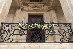 Adorned with flowers balcony of the Church of St Catherine in ca. Adorned with white flowers balcony of the Church of St Catherine in capital of Malta - Valletta Stock Image