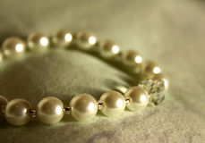 Adornment. String of creamy pearls (wristlet royalty free stock photography