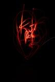 Adorno rojo abstracto de la pintura de la luz anaranjada en fondo negro Imagen de archivo