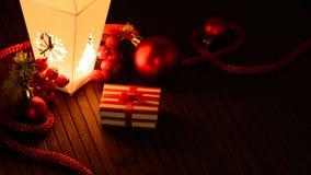 Adornos dispuestos de la Navidad y pequeña actual caja a la luz de la linterna Imagen de archivo