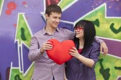 Ados avec le coeur près du mur de graffiti. Photo libre de droits
