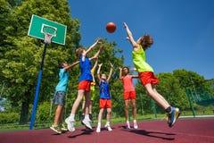Ados dans le saut jouant le match de basket ensemble Photos libres de droits