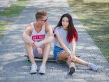 Ados datant en parc, belle fille et camarade s'asseyant sur un longboard sur un fond brouillé naturel Photo libre de droits