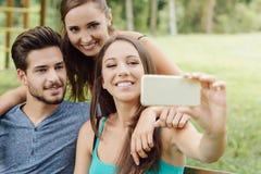 Ados gais au parc prenant des selfies Photographie stock
