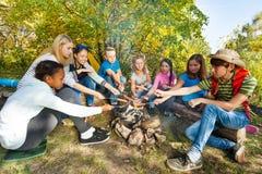 Ados grillant des saucisses sur la fin de séance de terrain de camping Photos stock
