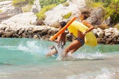 Ados heureux sautant dans la mer avec l'anneau gonflable Photographie stock