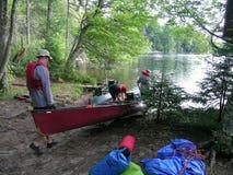 Ados mettant un canoë sur le lac Image libre de droits