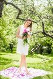Adoucissez la femme heureuse de brune avec le bouquet des pivoines dedans parmi les arbres par jour ensoleillé Photographie stock