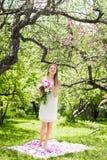 Adoucissez la femme heureuse de brune avec le bouquet des pivoines dedans parmi les arbres par jour ensoleillé Photo stock
