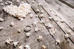 Adoucissez les fleurs blanches de forme de coeur avec l'anneau sur la table en bois Photos libres de droits