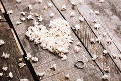 Adoucissez les fleurs blanches de forme de coeur avec l'anneau sur la table en bois Image libre de droits