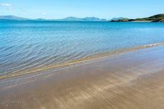 Adoucissez les vagues sur la plage sablonneuse d'Anglesey et de montagnes de Snowdonia - 3 Photos stock