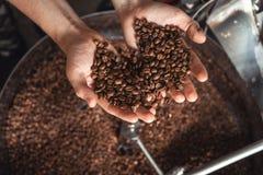 Adra świeży kawowy prażak w rękach na tle prażalnik zdjęcia stock