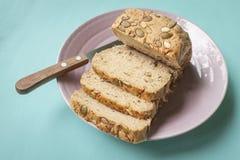 adra Chlebowy plasterek z nożem na ceramicznym talerzu Zdjęcie Royalty Free