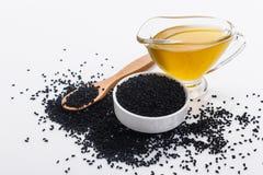 Adra czarny olej na nieociosanym tle i kmin obraz stock