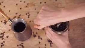 Adra kawa nalewają w kawowego ostrzarza Od zbiornika dla przechować kawę, wp8lywy kawy adra i nalewają w rękę zbiory