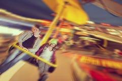 Adrenalin ride. Beautiful, young couple having fun at an amusement park Royalty Free Stock Photos