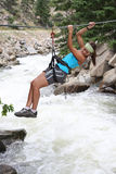 Adrenaline. An attractice and atletic girl makes tyrolean traverse over a rushing river Stock Image