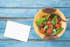 Adreskaartje op blauw houten bureau met voedsel Royalty-vrije Stock Fotografie