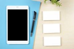 Adreskaartjespatie, smartphone of tabletpc, bloem en pen bij de bovenkantmening van de bureaulijst Collectieve kantoorbehoeften Stock Foto's