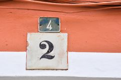 Adress number of the orange and white wall. Vintage Numbers, arabic numbers with beautiful design royalty free stock photo