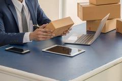 Adresse d'écriture d'homme d'affaires sur le paquet photo stock