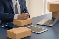 Adresse d'écriture d'homme d'affaires sur le paquet Les PME commencent  photographie stock libre de droits
