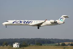 Adria Airways Bombardier CRJ900. Slovenian Adria Airways Bombardier CRJ900 with registration S5-AAO on short final for runway 14 of Zurich Airport stock photo