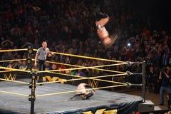 Adrian Neville mueve de un tirón en el aire mientras que él realiza la flecha roja como Foto de archivo