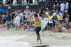 Adriano De Souza - Quicksilver Pro. Adriano De Souza running back to the competition area after catching a wave in his heat at the Quicksilver Pro 2011 held at Royalty Free Stock Images