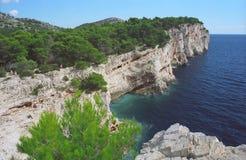 Adriatic cliff coast Croatia. Sunny Adriatic, blue sea, blue sky, coast cliff and evergreen pine - Croatia Royalty Free Stock Image