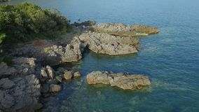 Flying Low Over Adriatic Coast Line With Stones Green Bushes And Clear Sea Water. Adriatic sea coast line with small stones, green bushes and clear sea water stock footage