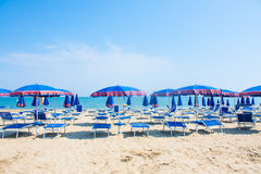 Adriatic Sea coast view. Seashore of Italy, summer umbrellas on sandy beach with clouds on horizon. Stock Photos
