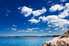 Adriatic Sea coastline. Under blue sky. Stony beach of Rovinj - tourist town on Croatian coast Stock Photo