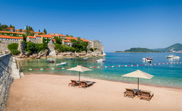 Adriatic sea luxury sand beach with chaise-longue chairs and umbrellas. Near the Sveti Stefan historical town on a small island. Montenegro stock photography
